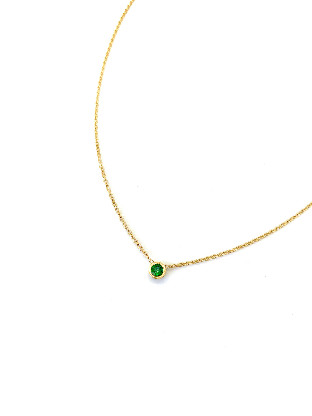 Materials include a 16-inch 14k yellow gold chain w/ a 3mm green garnet gemstone