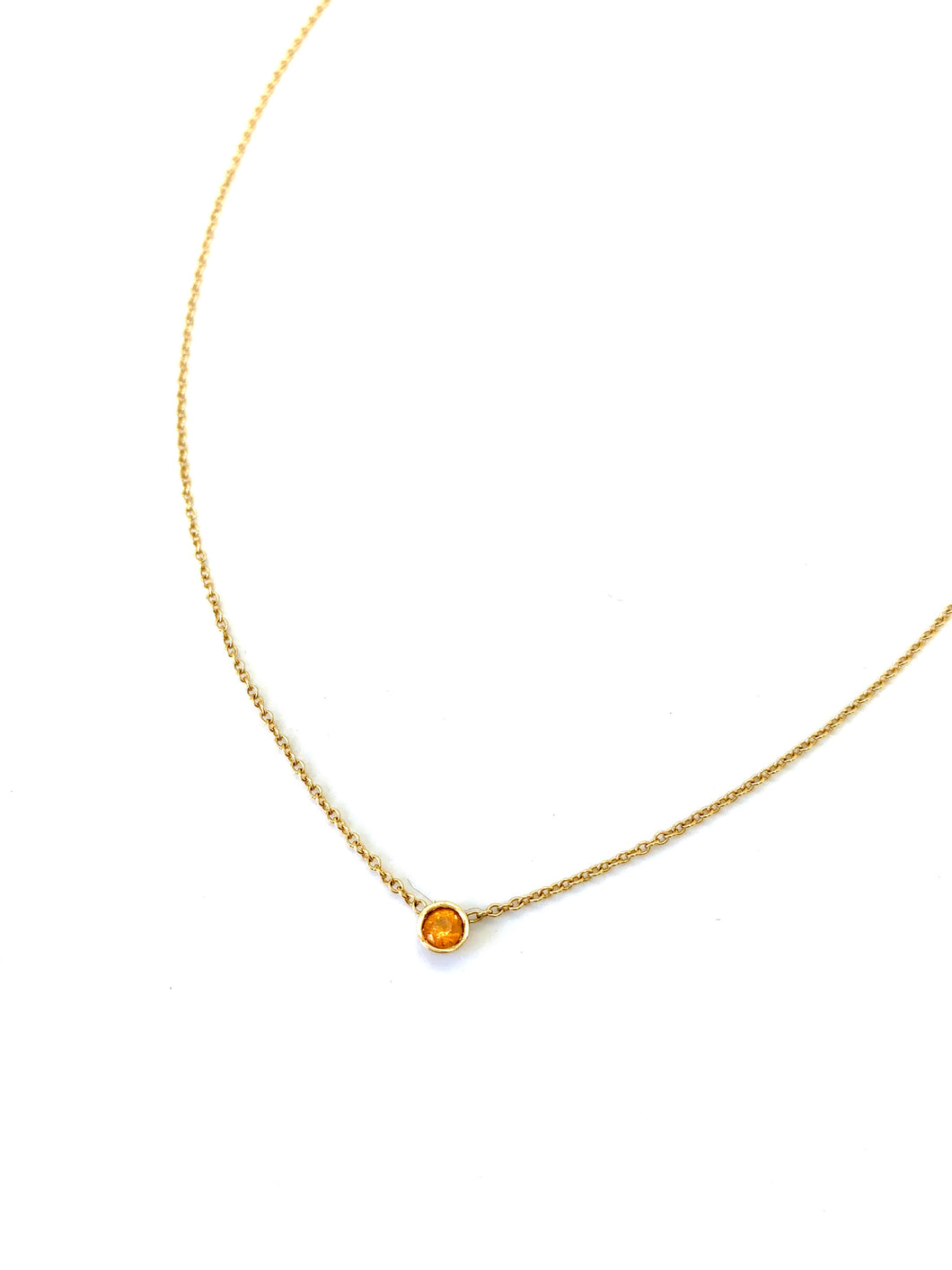 Materials include a 16-inch 14k yellow gold chain w/ a 3mm orange sapphire gemstone
