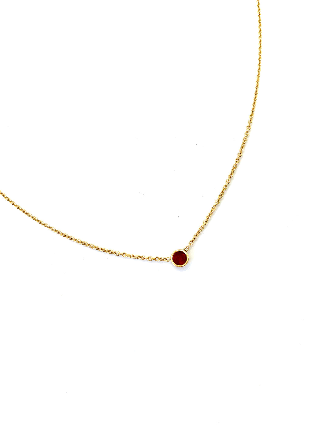 Materials include a 16-inch 14k yellow gold chain w/ a 3mm ruby gemstone