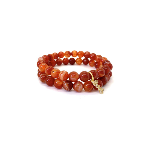 Bracelet materials include 8mm carnelian stones on an elastic cord w/ an 18k gold-plated script love charm that is adorned w/ Austrian crystals