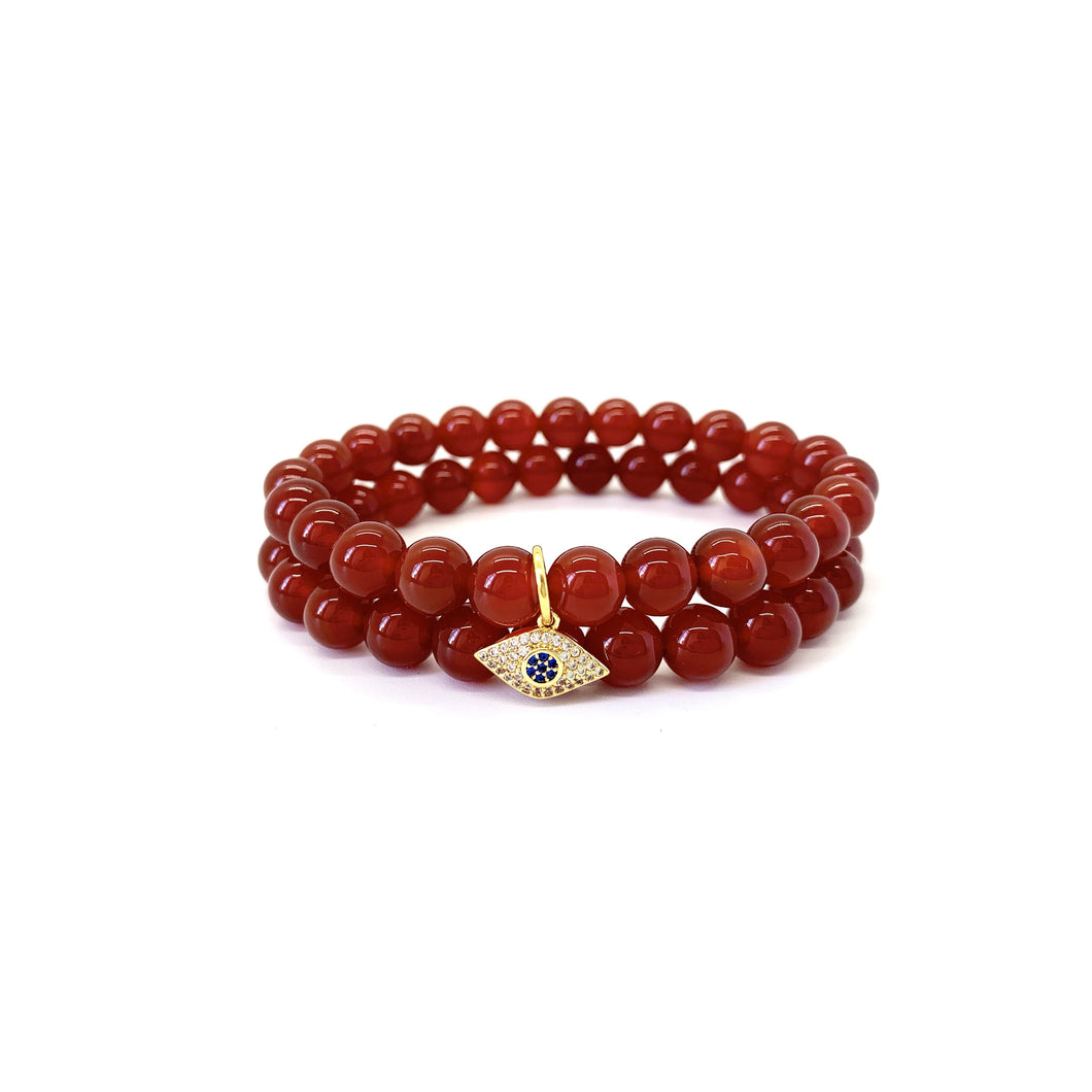 Bracelet materials include 8mm agate stones on an elastic cord w/ an 18k gold-plated eye charm that is adorned w/ Austrian crystals