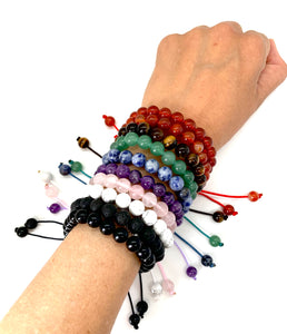 Choose the energy that you want or may need with our macrame bracelets! Styles include red agate for strength, carnelian for courage & creativity, tiger's eye for protection, aventurine for prosperity, sodalite for expression, amethyst for peace & healing, rose quartz for love, howlite for awareness, onyx for power, and lava for grounding.  Bracelet materials include 6mm stones on an adjustable string that measures 6-9 inches to fit men, women & children. One size fits most.