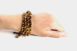 Tiger's Eye is a brown marbleized stone that offers protection to the wearer and is most associated with the solar plexus chakra. Materials include 108, 6mm tiger's eye stones that are strung on an elastic (stretch) cord for comfort & durability.  This mala is unisex and will likely wrap four times around the wrist for women & three for men. If worn as a necklace, it measures 28 inches.