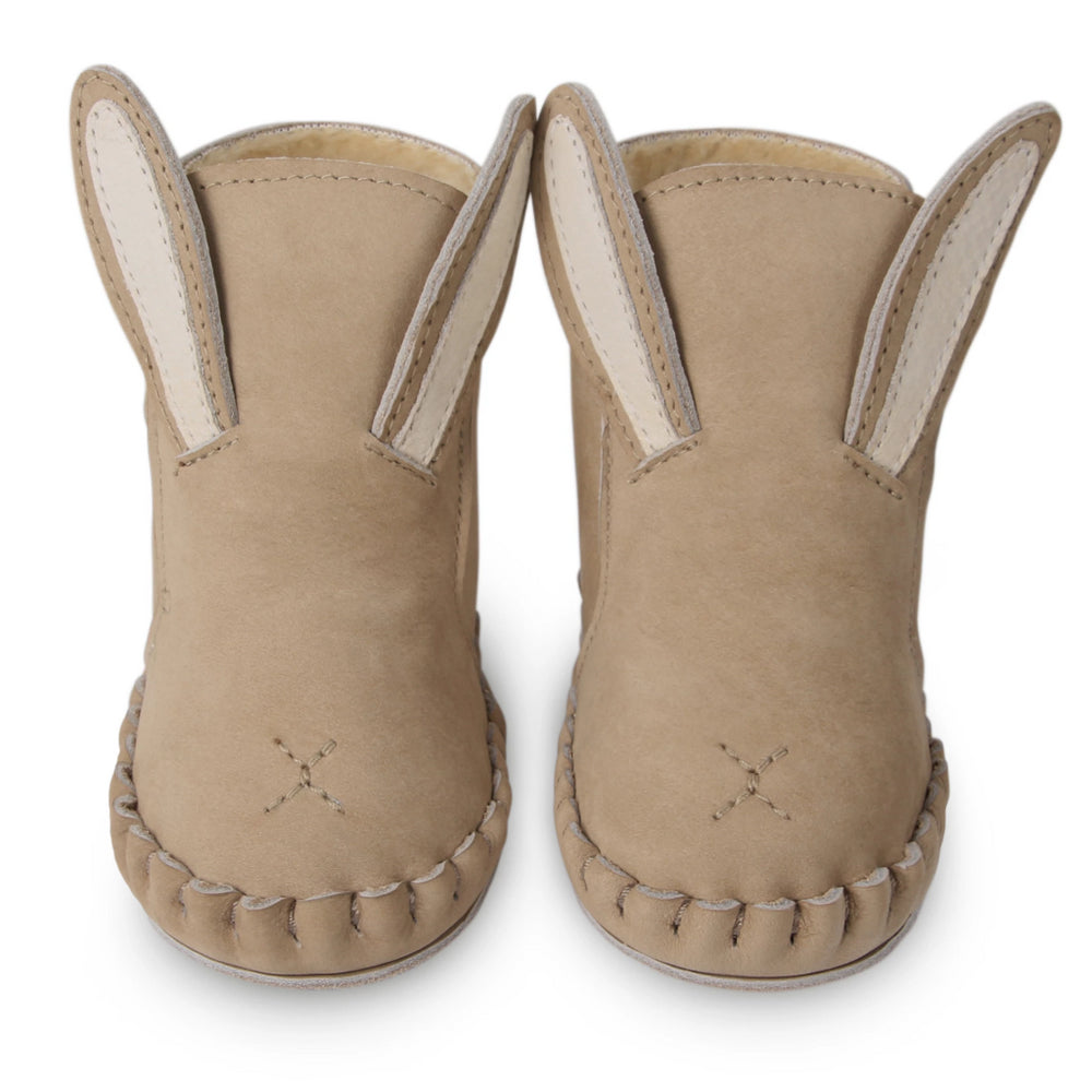 Nubuck Kapi bunny booties - Brand: Donsje Colour: Taupe Details: Handmade & Fairtrade Anti slip suede outsole (size: 0-6 & 6-12 months) Rubber flexible sole (size: 12-18 & 18-24 months) Composition:  100% Premium leather, Fully lined with faux fur, Velcro fastening strap *** Donsje donates a part of its profits to the Shining Star foundation in Kenya.