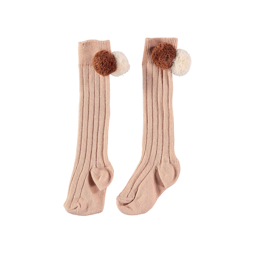 Dust rose knee length rib socks with two pom poms in beige and brown. Brand: Búho Details: Ribbed, Two pom-poms on each side Composition: 79% Cotton, 18% Polyamide, 3% Lycra Made in: France