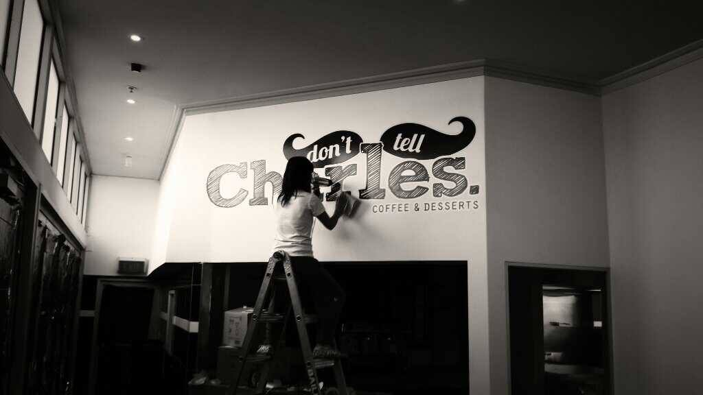 Thao installing Don't Tell Charles logo for the cafe