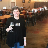 Sarah with a beer in her hand, with tables and taproom behind her