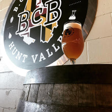 a pic of a glass of beer sitting on a boubon barrel with the BCB logo in the background