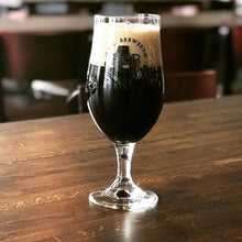 a glass of dark beer sitting on a wood table