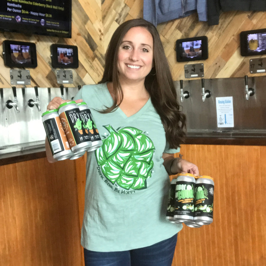 Sara wearing a short sleeved v neck ladies shirt with a hand drawn hop on the front with the words Drink beer. Be hoppy.  Shirt is a sea glass green and hop is various colors of green.  Sara is standing in front of our tap wall holding 2 4 packs of beer