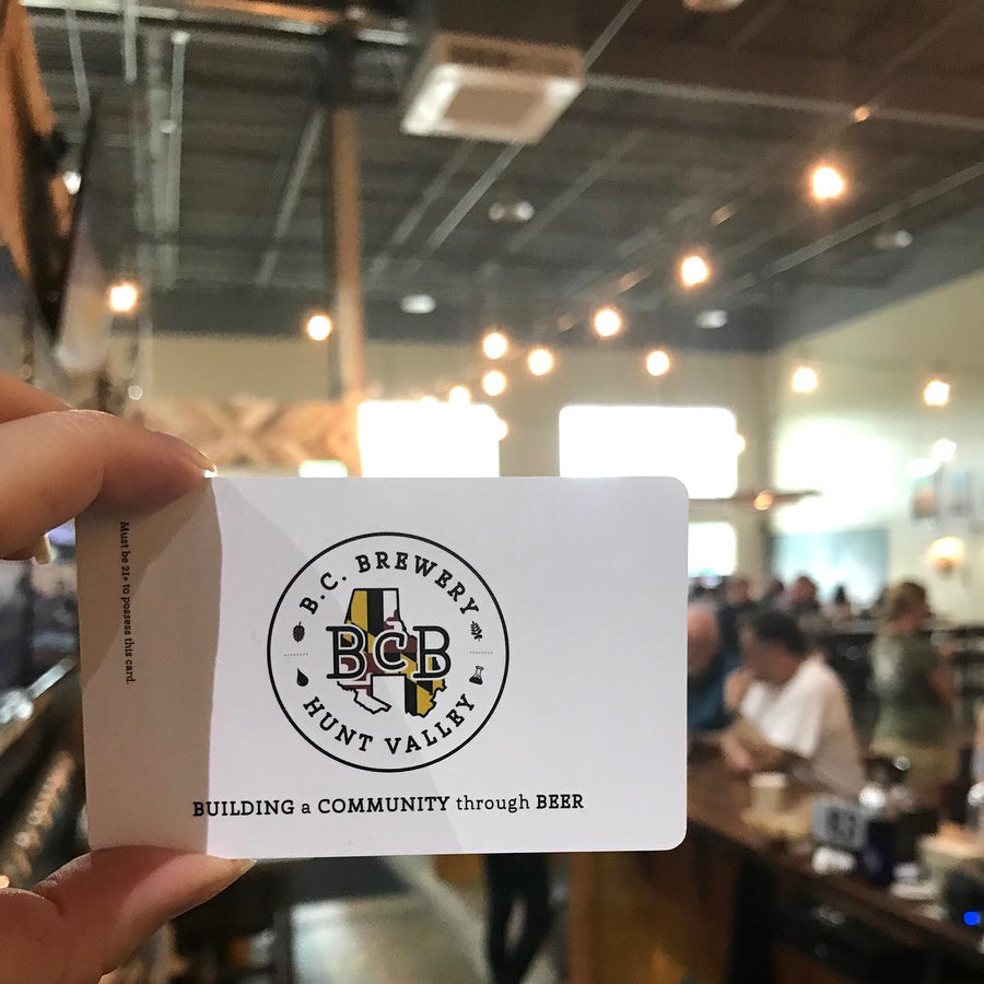 2 fingers holding a gift card with the taproom in the background