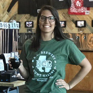 photo of monica wearing a green BCB shirt and holding a dark beer