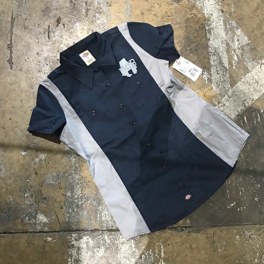 pic of a brewer shirt with buttons down the front, laying on the concrete floor