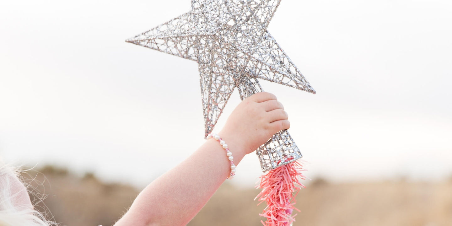 little girl wearing a Christmas pearl bracelet putting a silver star on a bright pink tree.