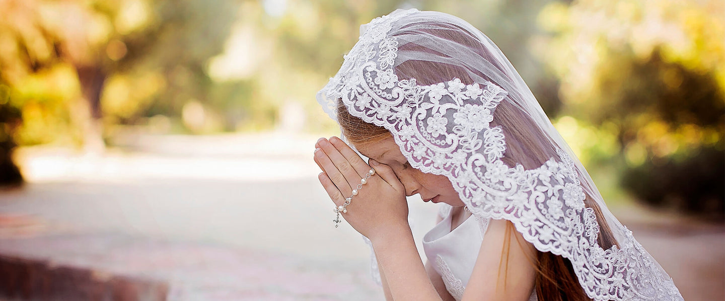 Girl praying with Little Girl's Pearls rosary bracelet for her First Holy Communion.