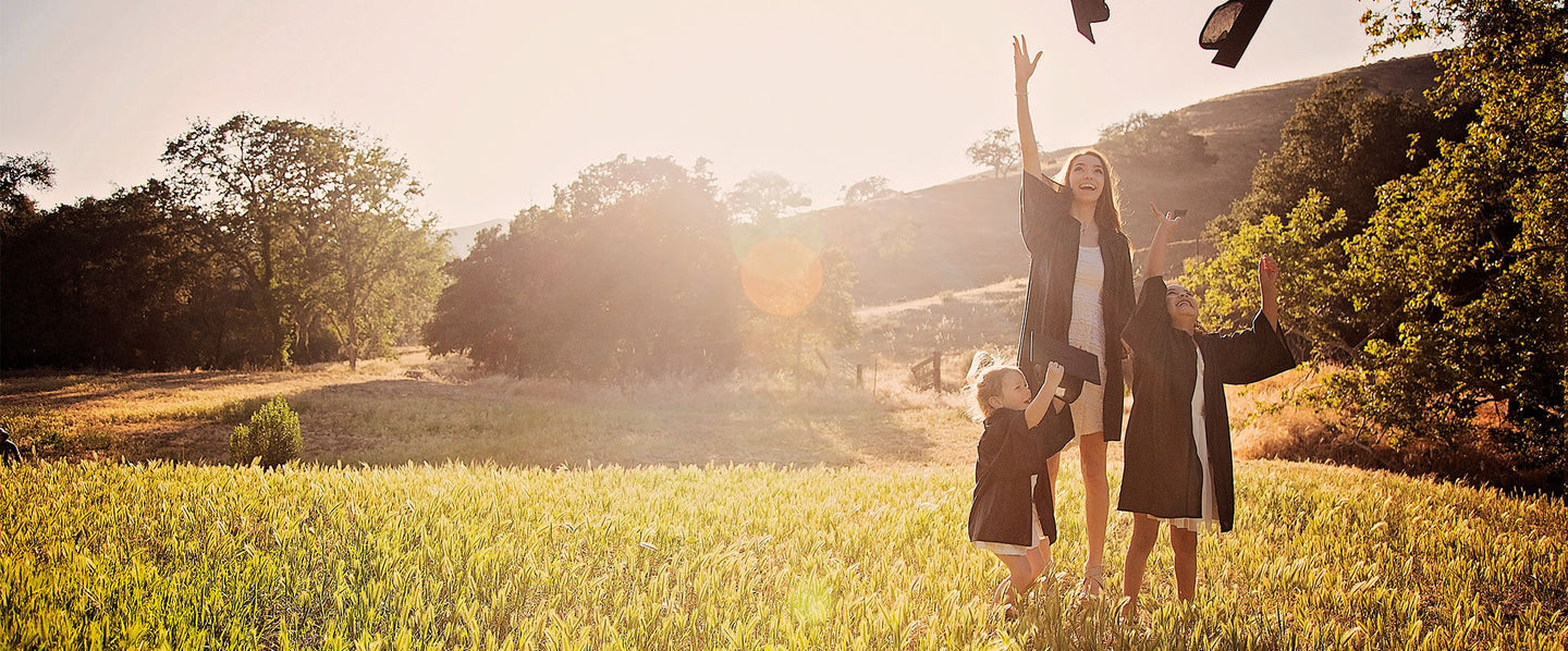 Three girls throwing their graduation hats in the air wearing little girl's pearls graduation pearl jewelry.