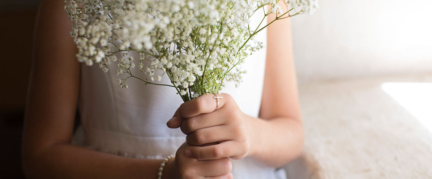 Girl holding baby's breath wearing an heirloom silver ring from Little Girl's Pearls.