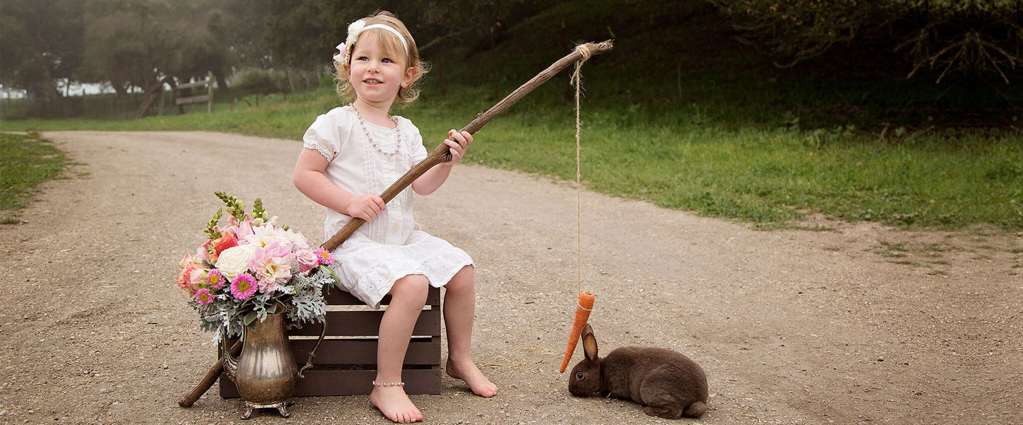 Girl in Easter Clothes and pearl necklace and anklet feeding a bunny a carrot on a string.