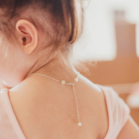 Little girl wearing a pink leotard. Silver chain necklace with pearls and an extension down her back.