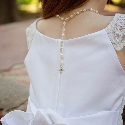 Little girl in First Communion dress with cross pearl necklace on back