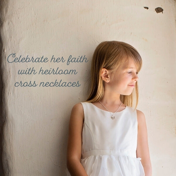celebrate her faith with heirloom cross necklaces - little girl in a white Easter dress wearing a keepsake silver heart cross necklace from Little Girl's Pearls.