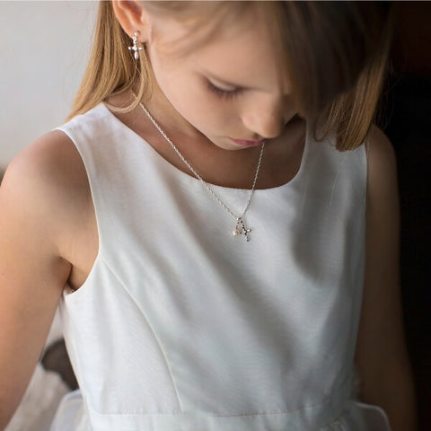 Little girl in white First Communion dress wearing cross necklace