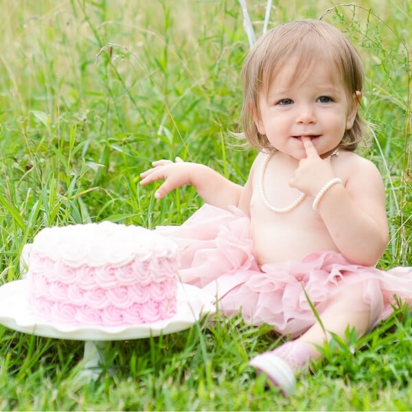 Little girl in pink tutu wearing pearl necklace next to a pink cake