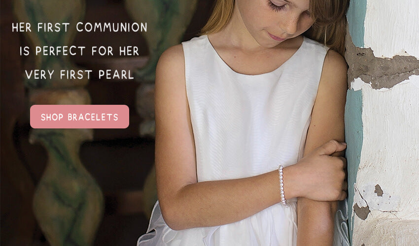 Little girl wearing a pearl bracelet for her Catholic first holy communion occasion.