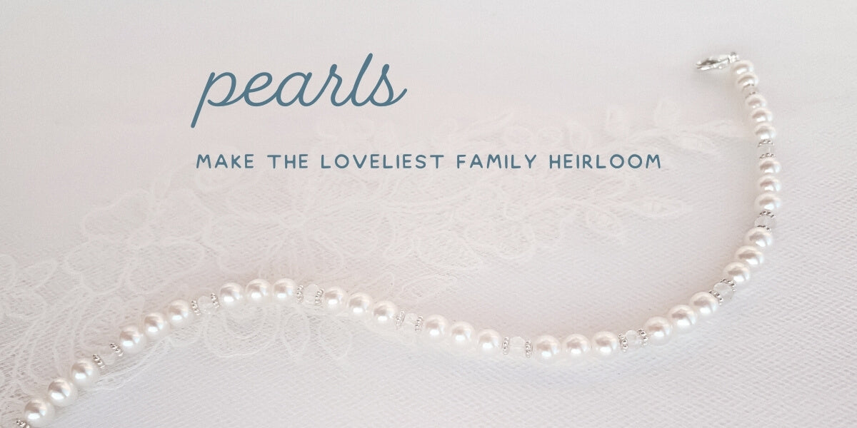 pearl and birthstone necklace with silver daisies draped on bridal lace. words say pearls make the loveliest family heirloom.