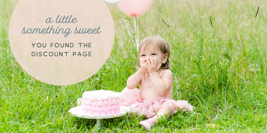 words say a little something sweet, you found the discount page. Little girl sitting in a field wearing a little girls pearls jewelry set for her pink ruffle smash cake session with balloons.