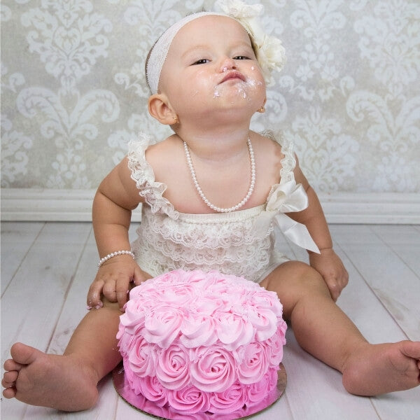 Girl's first birthday pink cake smash wearing pearl necklace