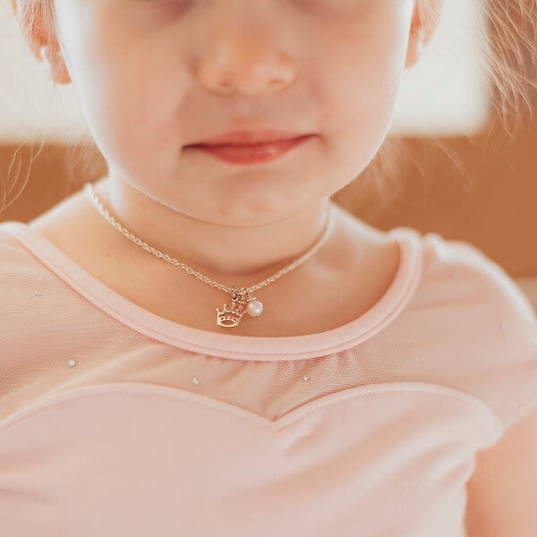 Little girl wearing pink leotard and necklace with pearl and crown