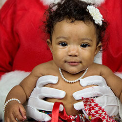 Toddler Girl wearing Little Girl's Pearls necklace being held by Santa for Christmas.