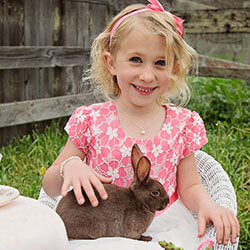 Little Girl holding a bunny and wearing a silver Easter necklace from Little Girl's Pearls.