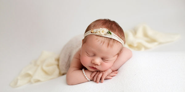 tiny baby girl draped in a blankie wearing a pearl bracelet.