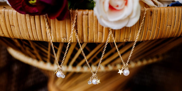 flower girl wish upon a star necklace with pearls and gold stars hanging from a wicker table topped with roses.
