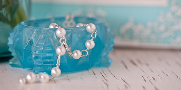 beautiful pearl and silver bracelet draped over a vintage blue French glass box.