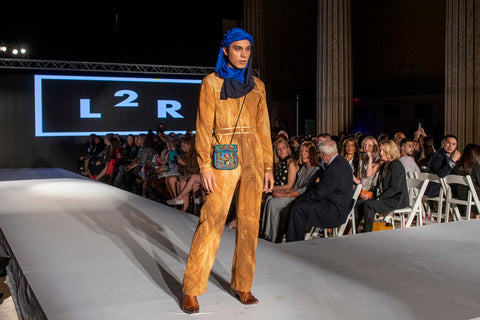 Karan model in desert overall and blue head scarf and blue cross body leather bag