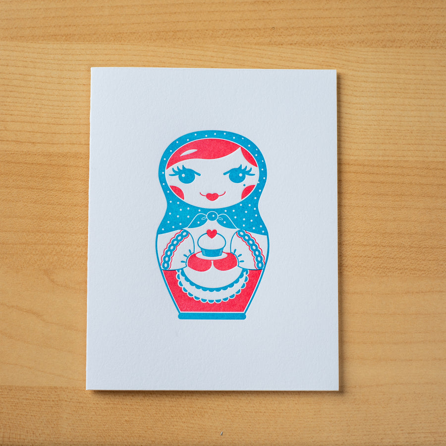 Letterpress birthday greeting card of nesting doll holding cupcake