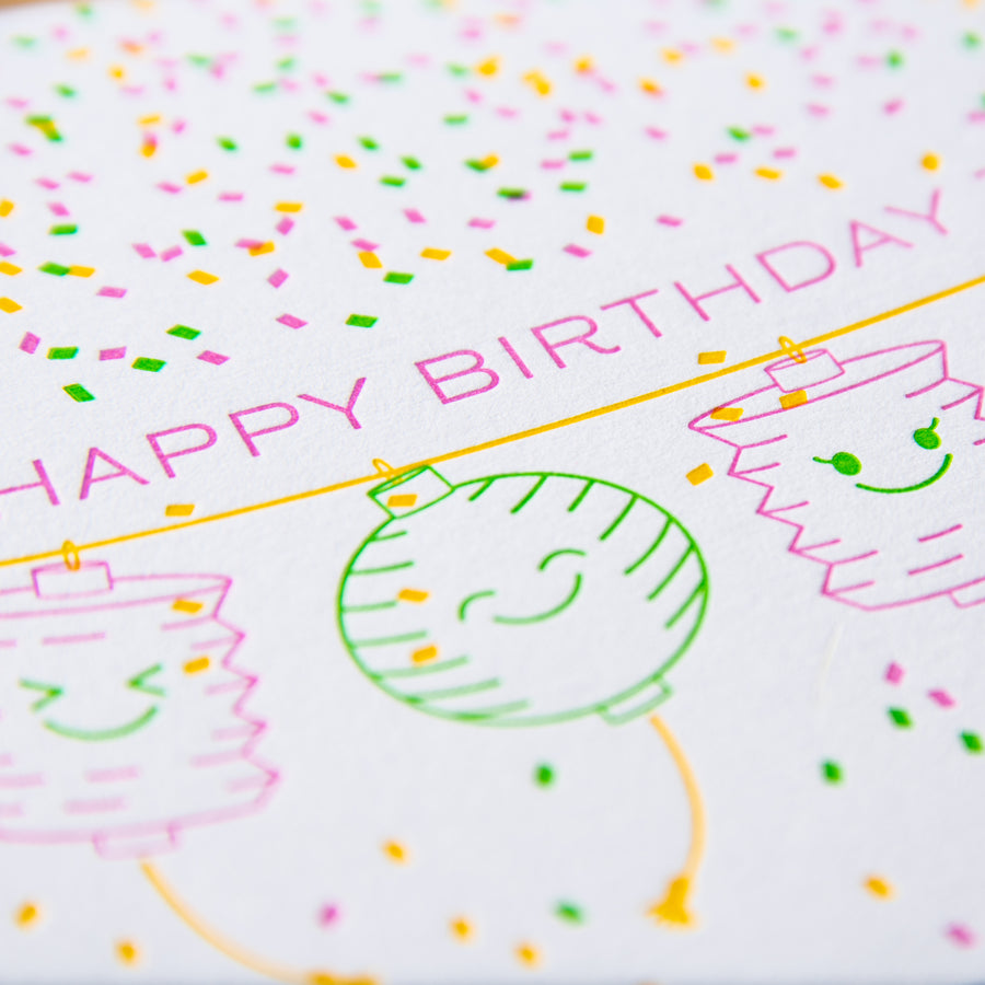 Letterpress birthday greeting card of paper lanterns and confetti