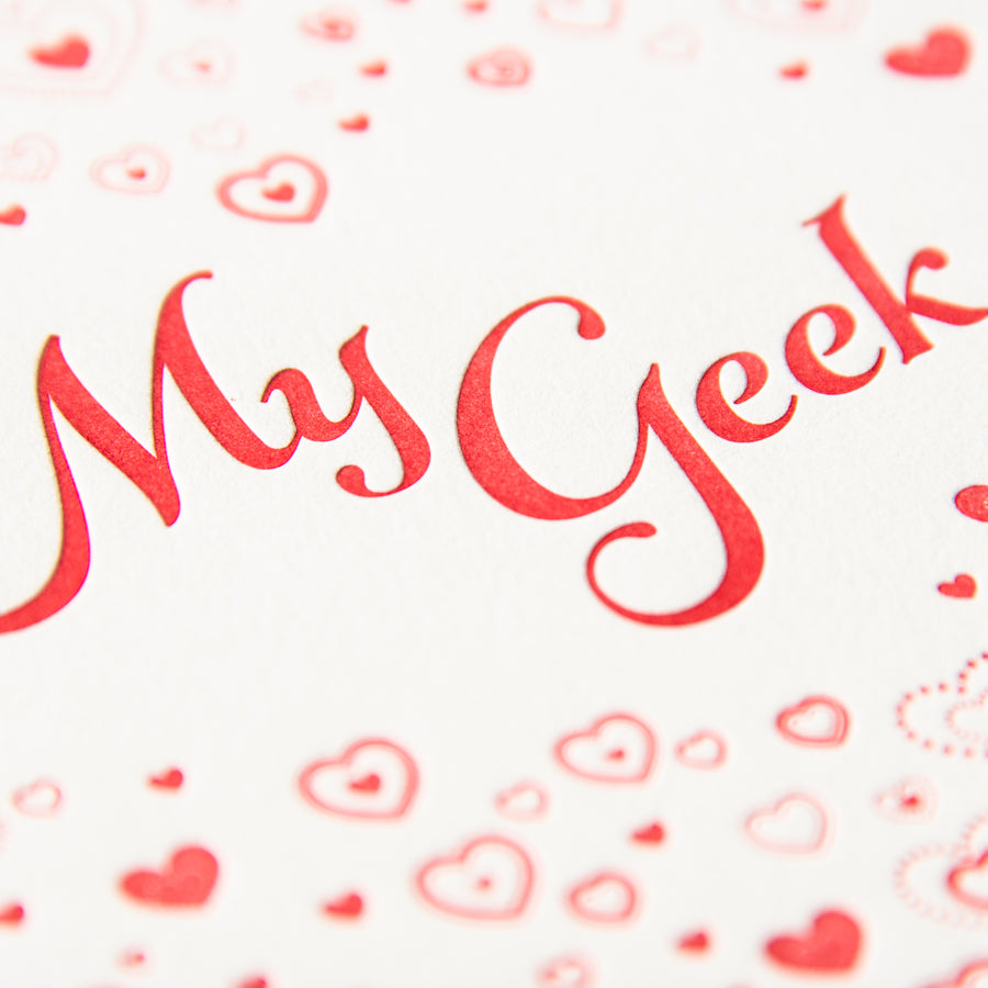 Letterpress Valentine greeting card with small red hearts encircling the phrase My Geek