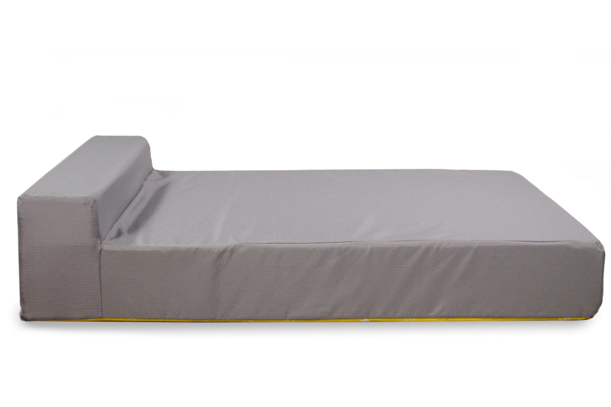 A gray K9 Ballistics mattress without a cover on a dark wooden floor