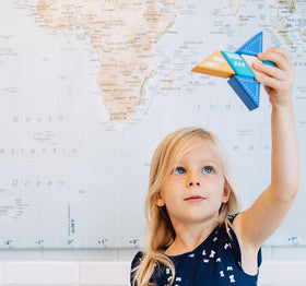 Blonde girl standing in front of a map plays with a plane made out of toy blocks