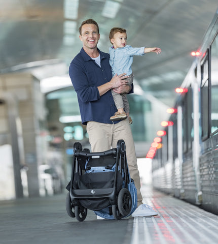 Man holding child while standing behind folded Stokke Beat on a train platform