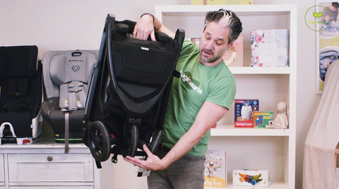 Man holding a folded Thule Spring stroller