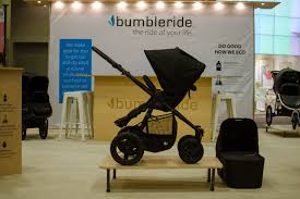 "Black Bumbleride Era stroller on top of a wooden platform with a sign reading ""Bumbleride"" in the background."