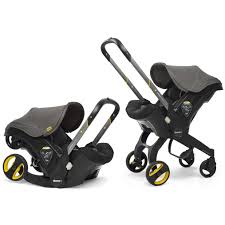 Two black and yellow Doona Infant Car Seat Strollers, one in its car seat configuration and the other in its stroller configuration