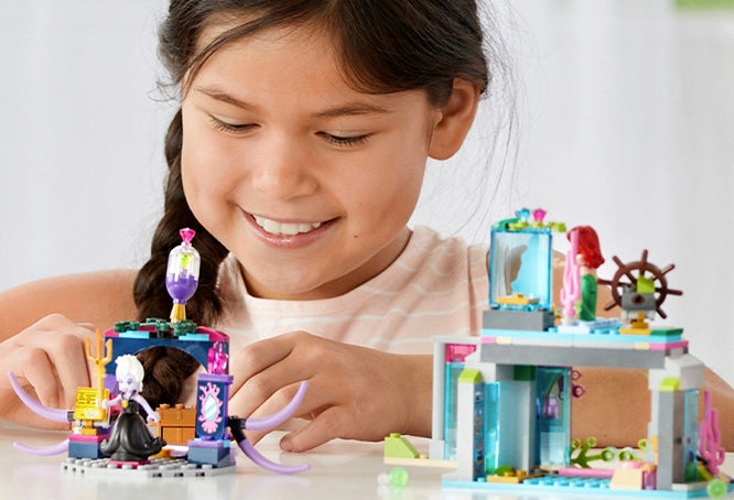 A child smiling at the Disney Little Mermaid Lego set