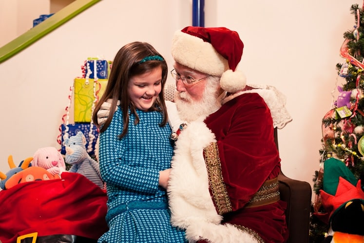 A girl in a blue dress sits on Santa's lap; presents wrapped in Magic Beans wrapping paper, a sack full of toys, and a Christmas tree are in the background.