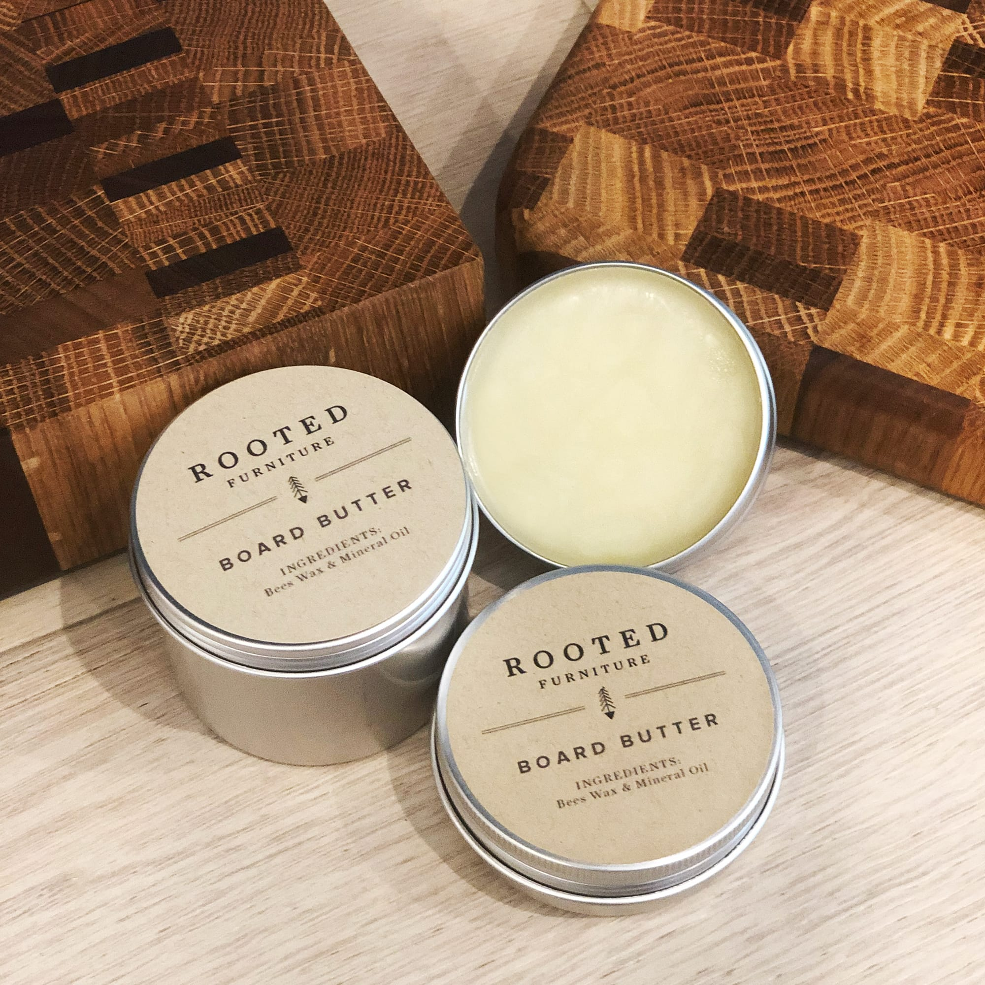 Rooted Board Butter in a tin next to two cutting boards